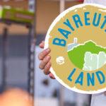 """Junger Mann hält """"Bayreuther Land Logo"""" in den Händen."""